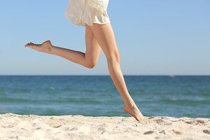Beautiful woman long legs jumping on the beach.jpg