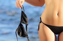 Close up of a woman on the beach in topless holding the bikini bra.jpg