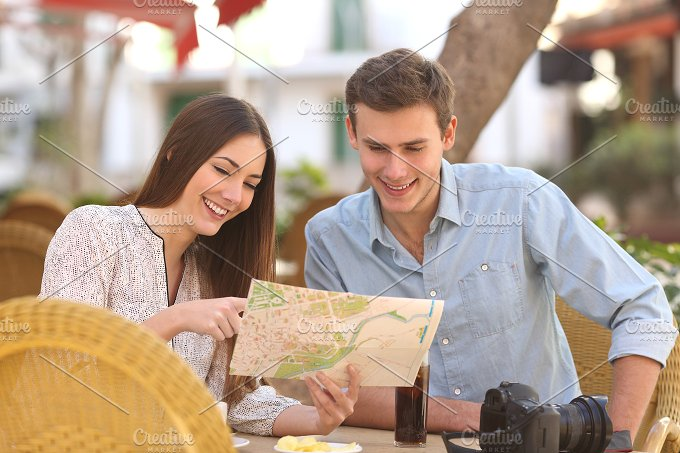 Couple tourists consulting a guide in a restaurant.jpg - Holidays