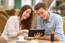 Couple watching media in a tablet in a restaurant.jpg