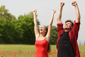 Euphoric couple raising arms in the country.jpg