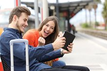 Euphoric couple playing game in a tablet in a train station.jpg