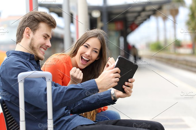Euphoric couple playing game in a tablet in a train station.jpg - Technology
