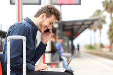 Freelancer working with a laptop and phone in a train station.jpg