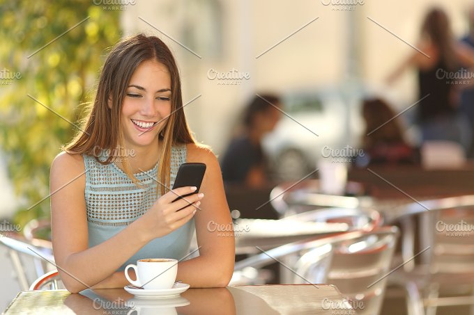 Girl texting on the phone in a restaurant.jpg - Technology