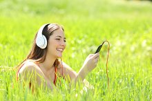 Girl listening music with headphones and smart phone in a field.jpg