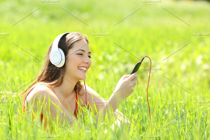 Girl listening music with headphones and smart phone in a field.jpg - Technology