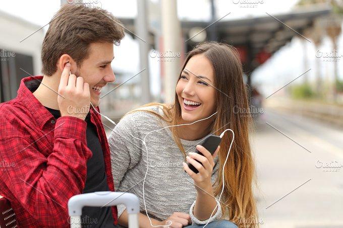 Happy couple of travelers sharing music on holidays.jpg - Technology