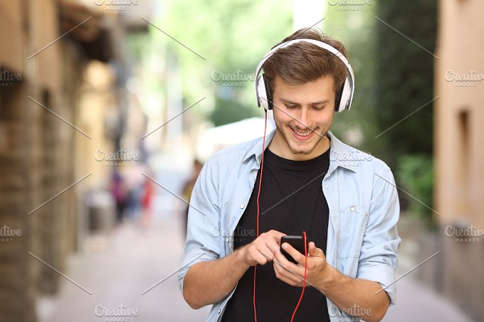 Guy walking and using a smart phone with headphones.jpg - Technology