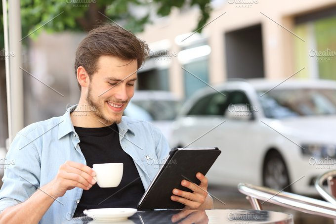 Man reading an ebook or tablet in a coffee shop.jpg - Technology