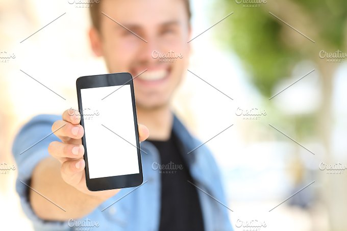 Man showing a blank phone screen in the street.jpg - Technology