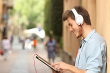 Man using a tablet with headphones on the street.jpg