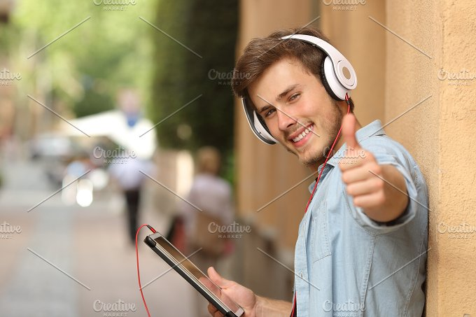 Man using a tablet with thumbs up in the street.jpg - Technology