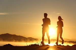 Silhouette of a couple running at sunset.jpg