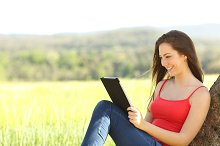 Relaxed woman reading an ebook in the country.jpg