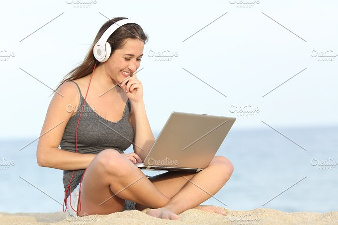 Student learning course with a laptop on the beach.jpg - Technology
