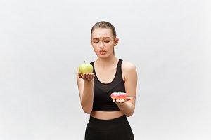 Young woman choosing between donut