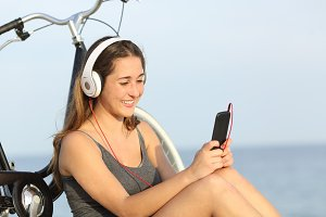 Teen girl listening music from a smart phone on the beach.jpg