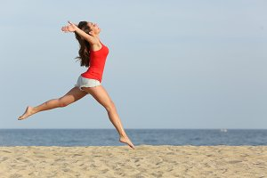 Teen girl in red jumping happy on the beach.jpg