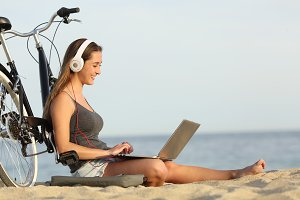 Teen girl studying with a laptop on the beach.jpg
