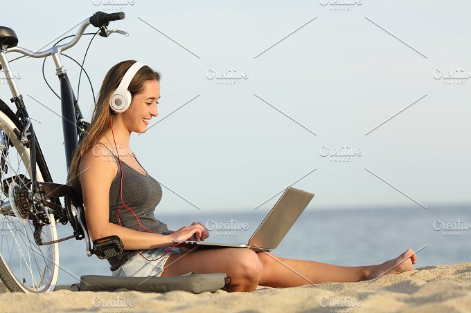 Teen girl studying with a laptop on the beach.jpg - Technology