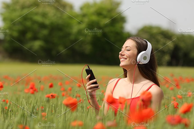 Woman breathing and listening music in a field.jpg - Technology