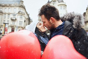 enamored couple in winter clothes is