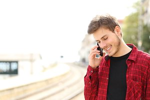 Teen guy calling on the mobile phone waiting a train.jpg