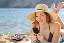 Woman on the beach texting a smart phone in summer.jpg
