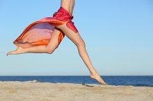 Woman legs jumping on the beach happy.jpg