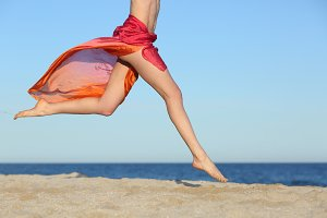 Woman legs jumping on the beach happy.jpg