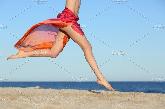 Woman legs jumping on the beach happy.jpg - Holidays