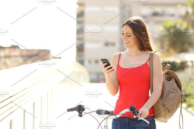 Woman using a smart phone walking with a bicycle.jpg - Technology