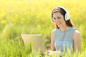 Woman with a laptop and headphones in a field.jpg