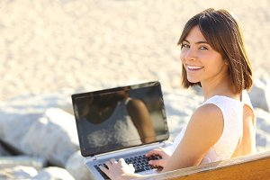 Woman typing on a laptop and looking at camera.jpg