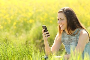 Woman using a smart phone in a green field.jpg