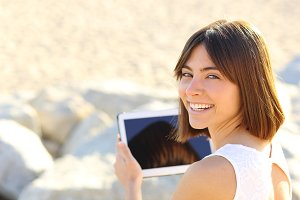 Woman using a tablet and looking at camera.jpg