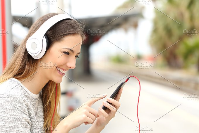 Teen girl listening to the music with headphones waiting a train.jpg - Technology