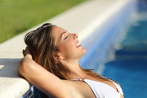 Happy woman relaxed in a swimming pool enjoying vacations.jpg