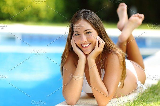 Happy girl posing wearing bikini on a pool side in summer vacations.jpg - Holidays