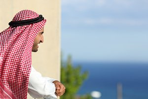 Arab saudi man looking the sea from a balcony of an hotel.jpg