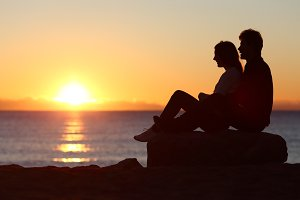 Couple silhouette sitting watching sun at sunset.jpg