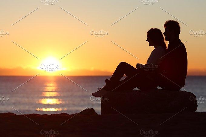 Couple silhouette sitting watching sun at sunset.jpg - People