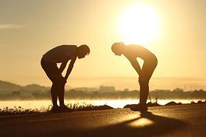Exhausted and tired fitness couple silhouettes at sunset.jpg