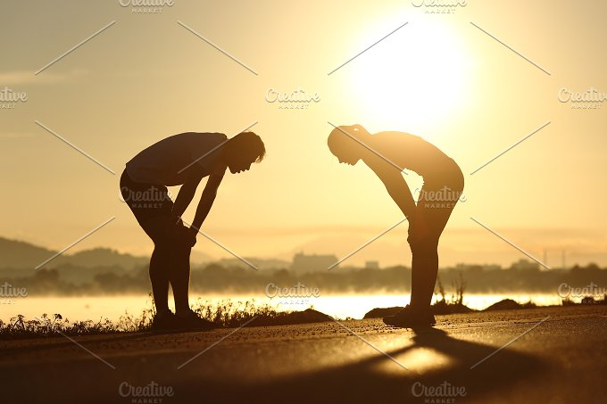 Exhausted and tired fitness couple silhouettes at sunset.jpg - People