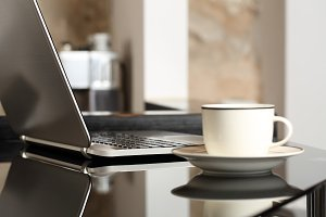 Laptop on a table with a cup of coffee.jpg