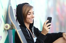 Young skater happy teen girl using a smart phone.jpg