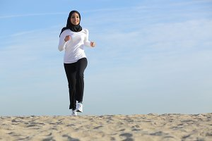 Front view of an arab saudi emirates woman running on the beach.jpg