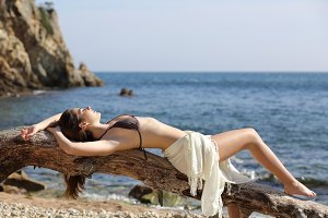 Beautiful woman sunbathing on the beach on vacations.jpg