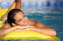 Girl enjoying summer vacations on a mattress in a pool and looking at side.jpg